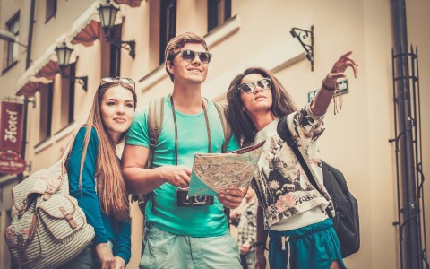 3 groups of friends touring the city, holding a map and pointing