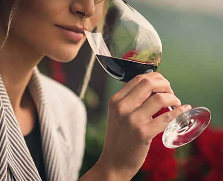 woman smelling red wine out of wine glass Image