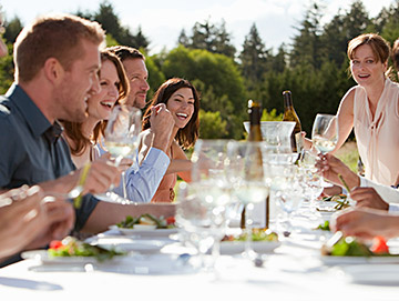 large group of people laughing at an outdoor lunch