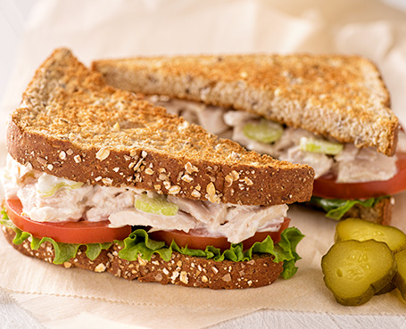 tuna sandwich on whole wheat bread and pickles Image