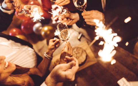 people holding sparklers and champagne flutes