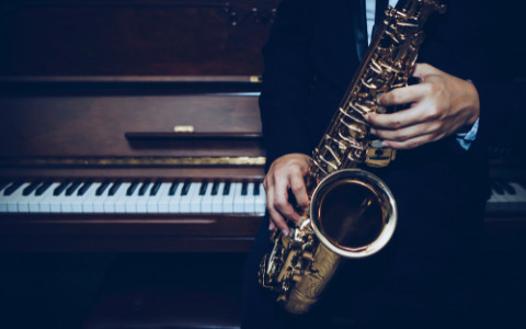 saxophone player in front of a piano