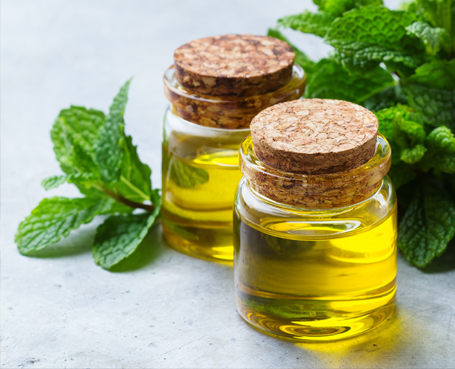 two glass containers of oil with a bunch of mint Image