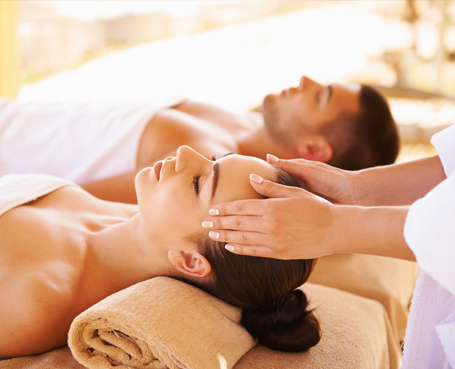 woman getting head massage and man laying on massage table in background Image
