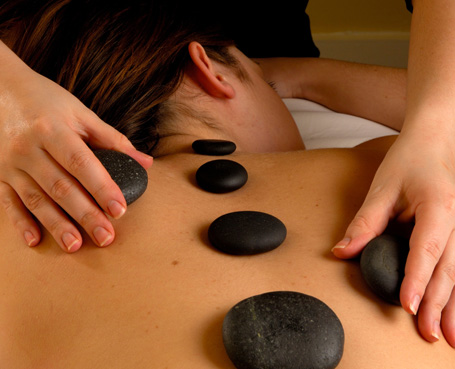 woman receiving back massage with six black stones on her back Image