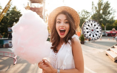 girl holding cotton candy at carnival fair