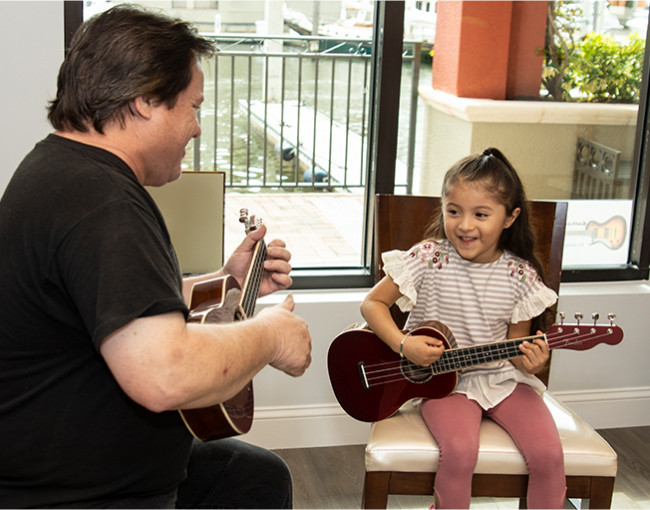 musician teaching little girl to play ukelele