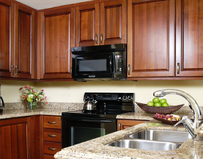 kitchen area with a fridge, microwave, oven, double sink, granite counters and dark wood cabinets