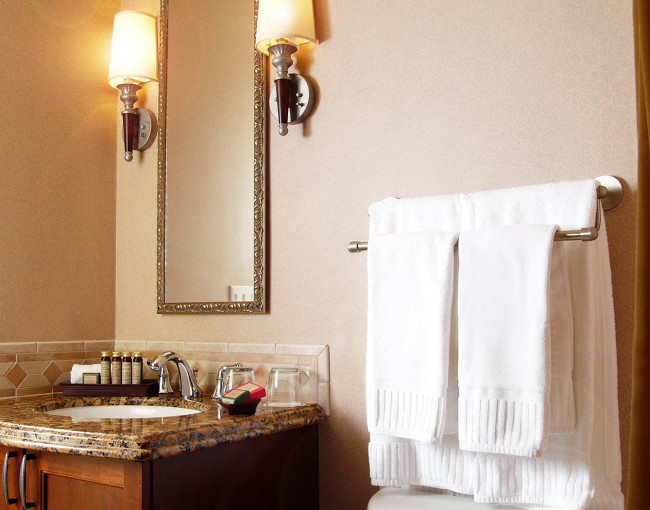 bathroom with a sink vanity, mirror, and towels draped on a rail overtop the toilet