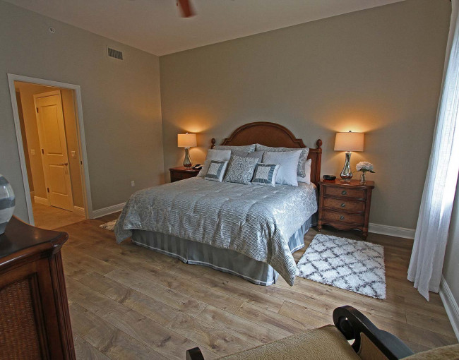 a king bed guestroom decorated with light blue and gray colors, two wooden nightstands with lamps and a wooden dresser