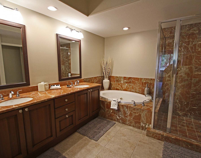 bathroom with a double sink vanity, mirrors, a large tub, and glass walk in shower