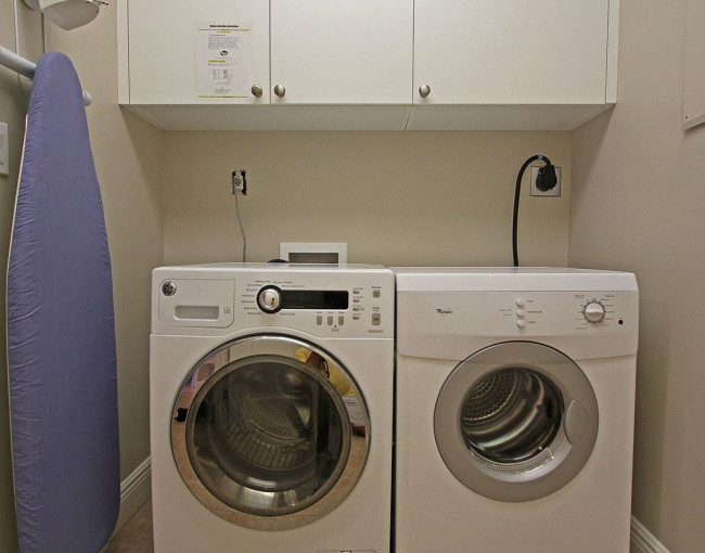 washer and dryer unit with overhead cabinets, iron and ironing board