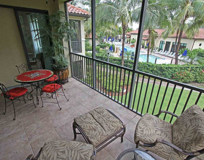 a covered second floor patio with cushioned chairs, table and chairs, and a view of the pool area