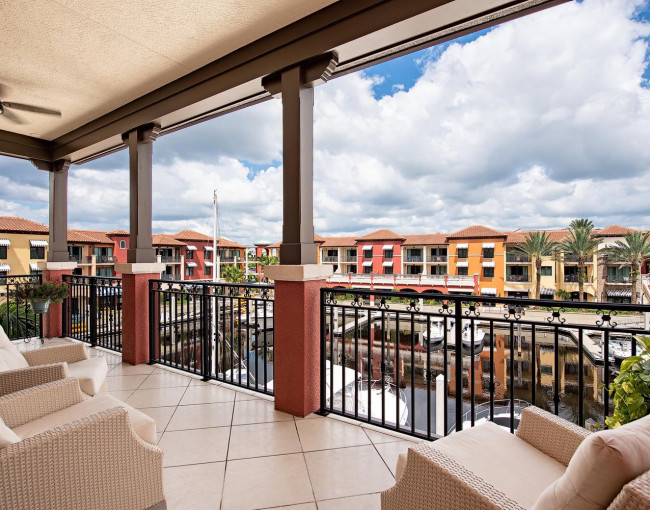 covered balcony with comfortable chairs overlooking the marina and colorful buildings