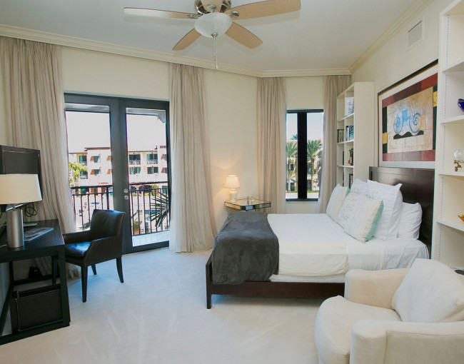 bedroom with white linens, tan cushioned chair, desk area, and a door leading to a balcony from the room
