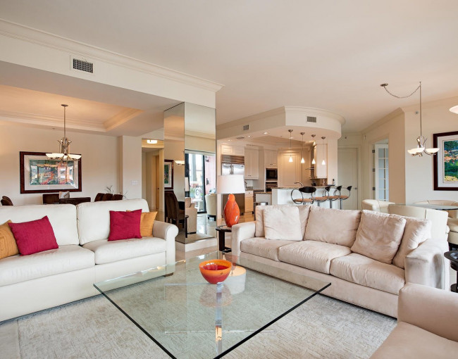 living room area with tan couches, glass coffee table, orange and red decorative pillows, and a view of the dining area and kitchen in the back