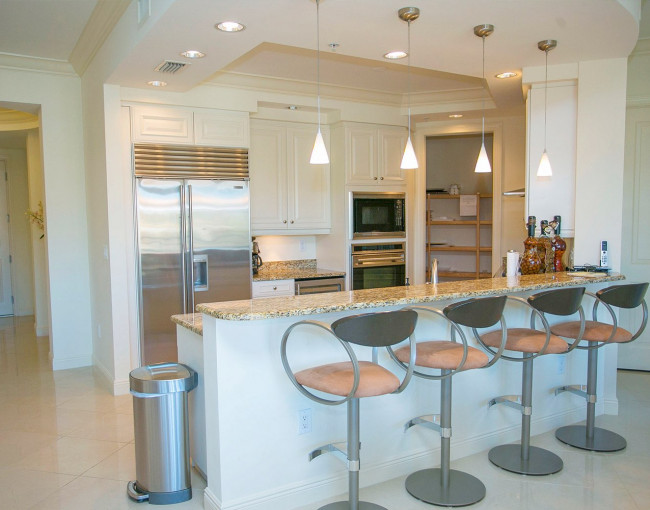 kitchen area with white cabinets, stainless steel appliances, and counter height chairs