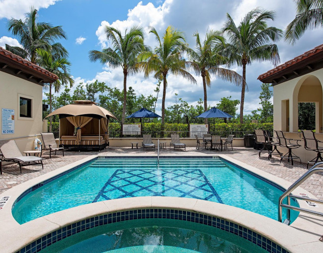 pool area with a hot tub, lounge chairs, cabana, and umbrellas