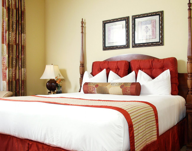 guest room with white linens, red accent colors, and doors leading to a balcony