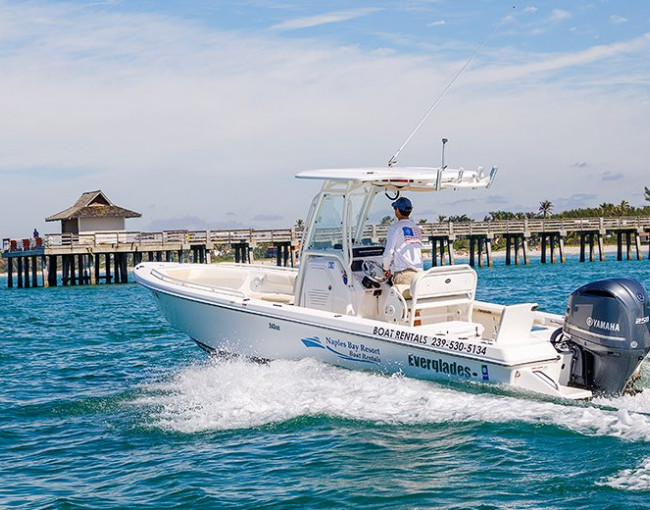 a man driving a white center console boat in the ocean near a pier