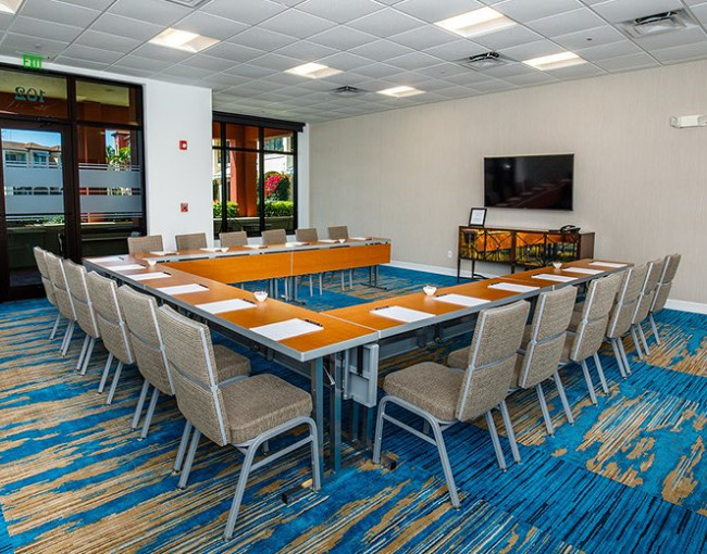 u-shaped conference table in a room with blue patterned carpet and a mounted tv on the wall