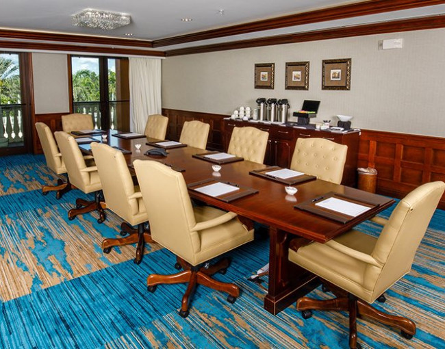 boardroom meeting table room with light brown leather swivel chairs
