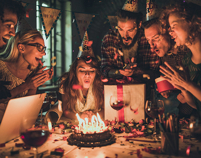 a woman blowing out her birthday cake candles surrounded by friends