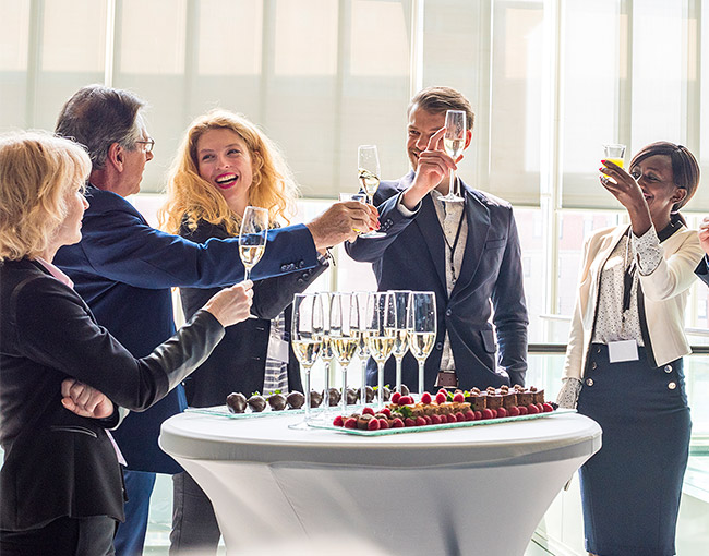 a group of business people standing around a cocktail tables holding up their glasses of champagne