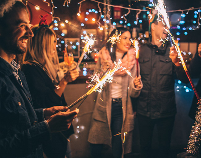 a group of friends holding sparklers at night