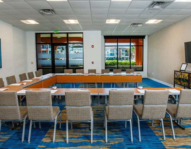 conference room with a u-shaped table, chairs, tv, and a blue patterned carpet floor