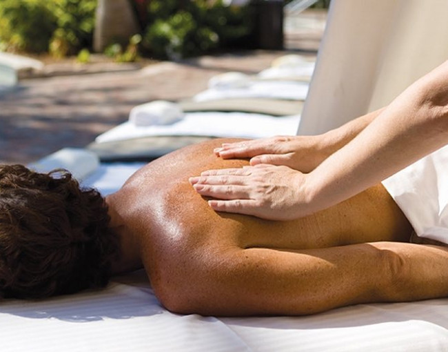 a woman getting a back massage on a spa table outside