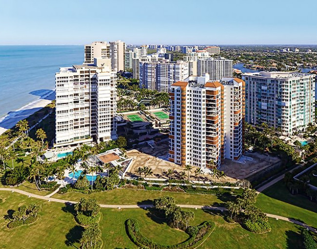 aerial view of tall buildings next to the ocean