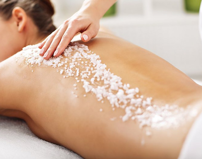 a woman at the spa getting a sugar scrub on her back