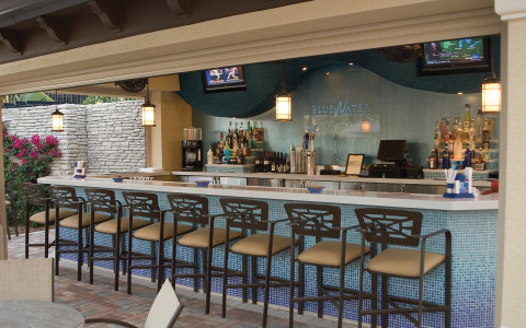 covered outdoor bar area with counter height chairs and two tvs behind the bar
