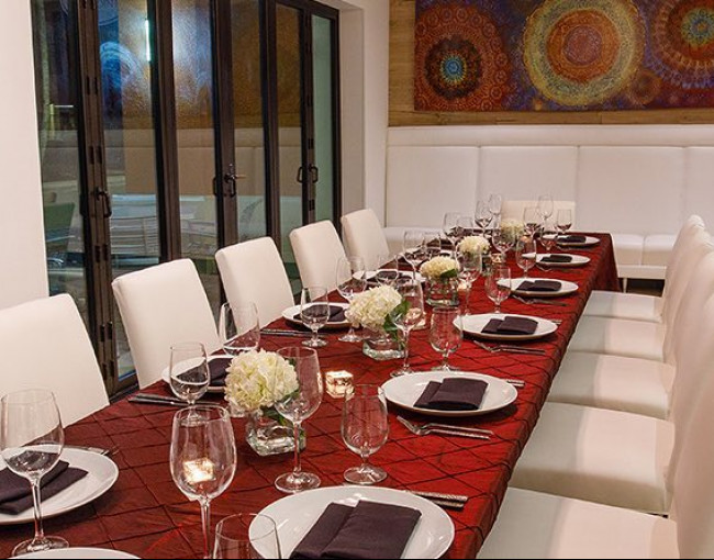 private dining room featuring a long table with a red tablecloth and white leather chairs