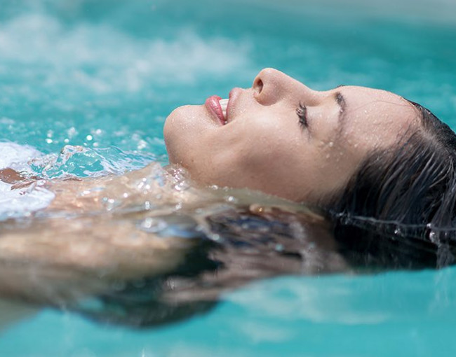 close up of a woman closing her eyes floating in a pool