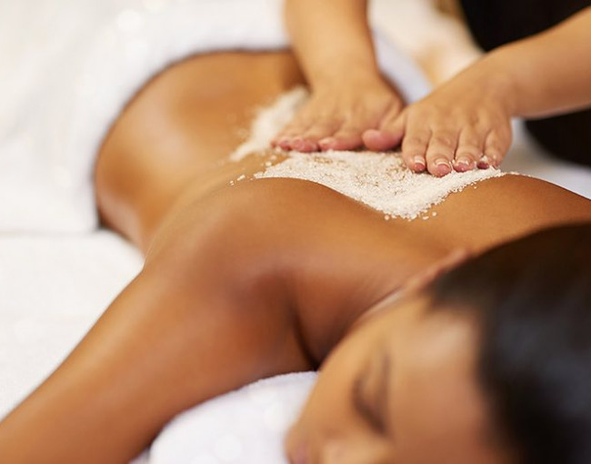 a woman getting a sugar scrub on her back at the spa