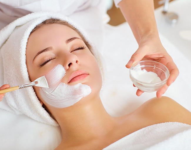 a spa employee applies a white mask with a brush to a woman getting a facial