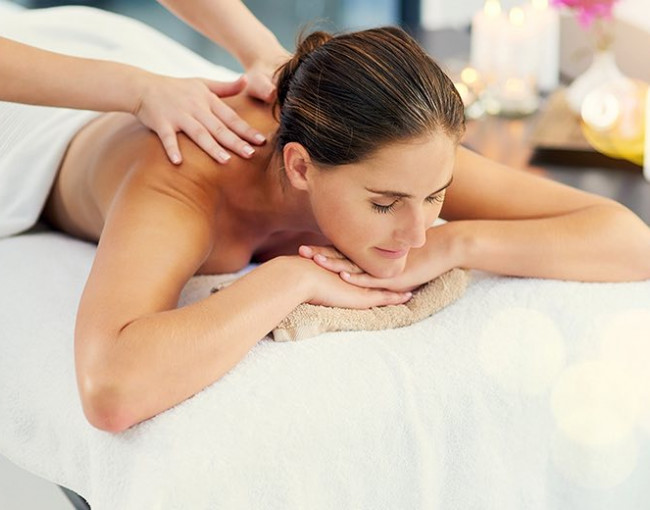 a woman gets a back massage at the spa