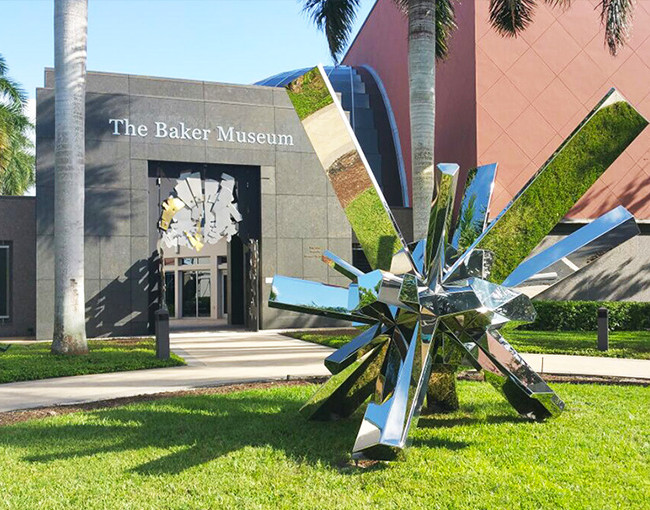 a large silver metal sculpture in the lawn in front of a museum building