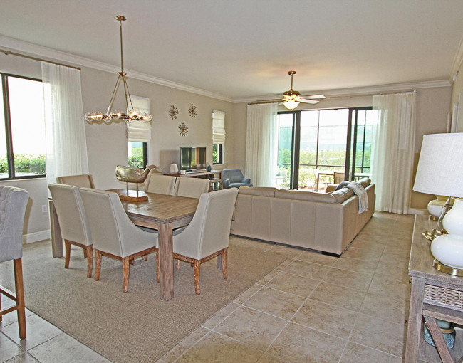 neutral colored living and dining room area with a six person dining table, couch, and sliding glass doors leading to a balcony