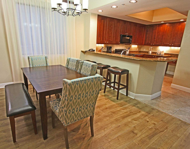 dining table that seats six people next to the kitchen area with three barstools at the counter