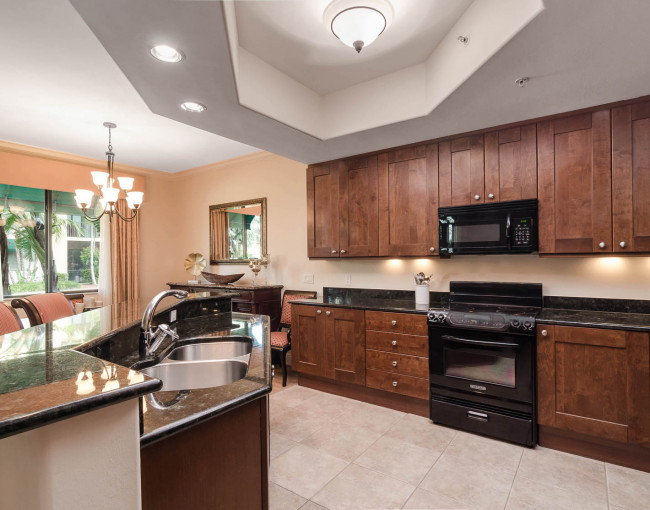 kitchen area with dark wood cabinets, black countertops, and a hightop island with barstools