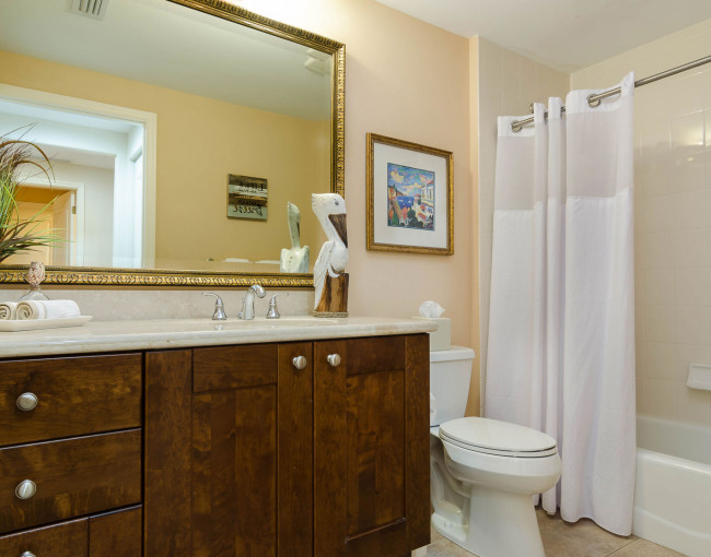 bathroom area with a white shower curtain and a vanity area with drawers and cabinets and vanity counter space