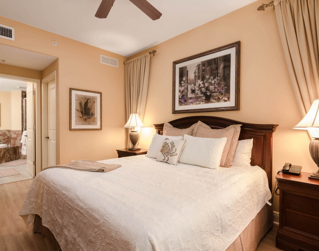 guest room featuring a white quilted bed, decorative drapes, two nightstands with lamps, and a view of the bathroom area