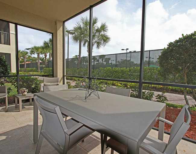screened-in outdoor patio with a patio table and chairs