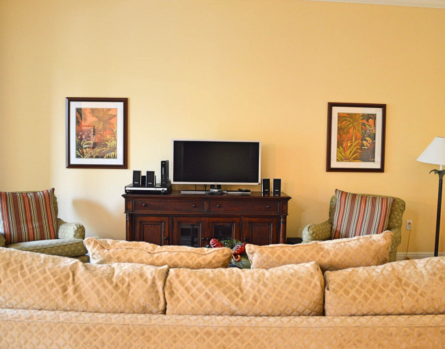 view of living room area from behind a tan couch with a view of the tv, two cushioned chairs, and two pictures on the wall
