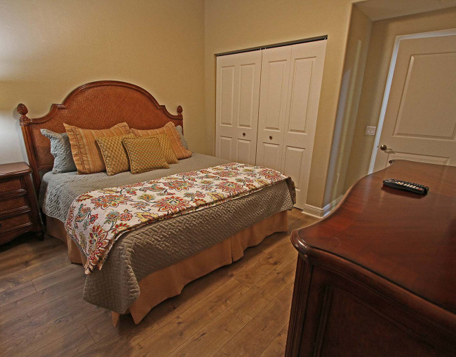 guest bedroom with dark wood furniture and gray quilt with a decorative quilt draped at the end of the bed