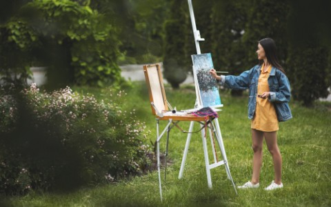 woman in yellow dress and denim jacket painting
