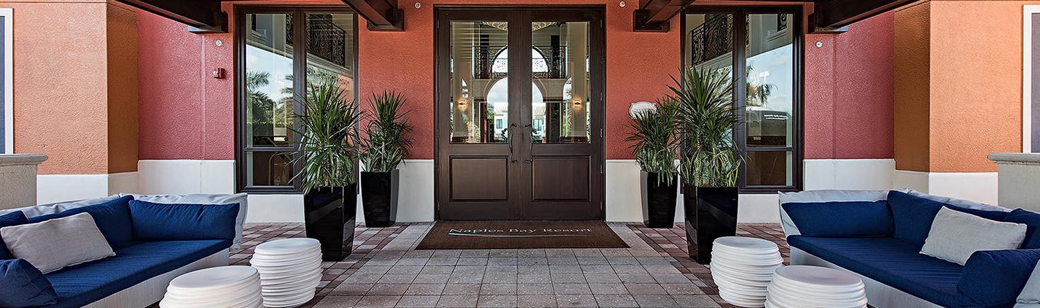 brown double door entrance to the resort with two navy blue cushioned couches lining the entrance walkway